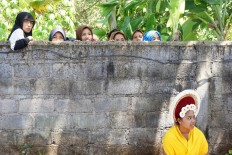 Muslim women living in a Muslim kampung in the middle of Bungaya village, take a peek over a wall at the Hindu ritual. About 20 Muslim men from Sasak Lombok joined the thousands of Hindu men to carry a mountain of produce, which can weigh between 2 to 7 metric tons. JP/ Luh De Suriyani