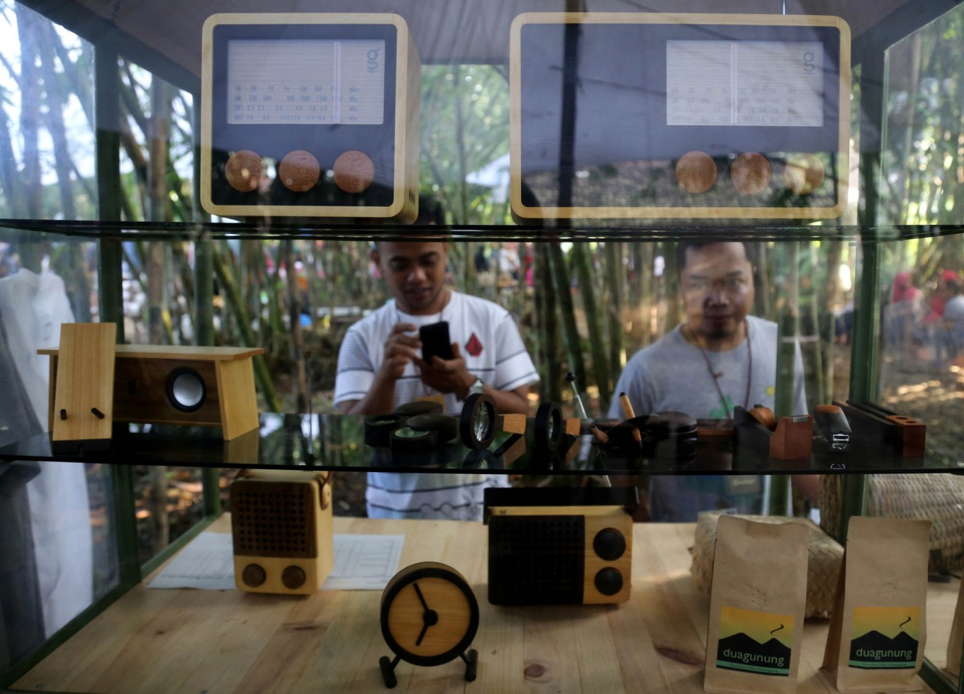 Visitors observe locally made wooden radios in a booth. JP/Ganug Nugroho Adi