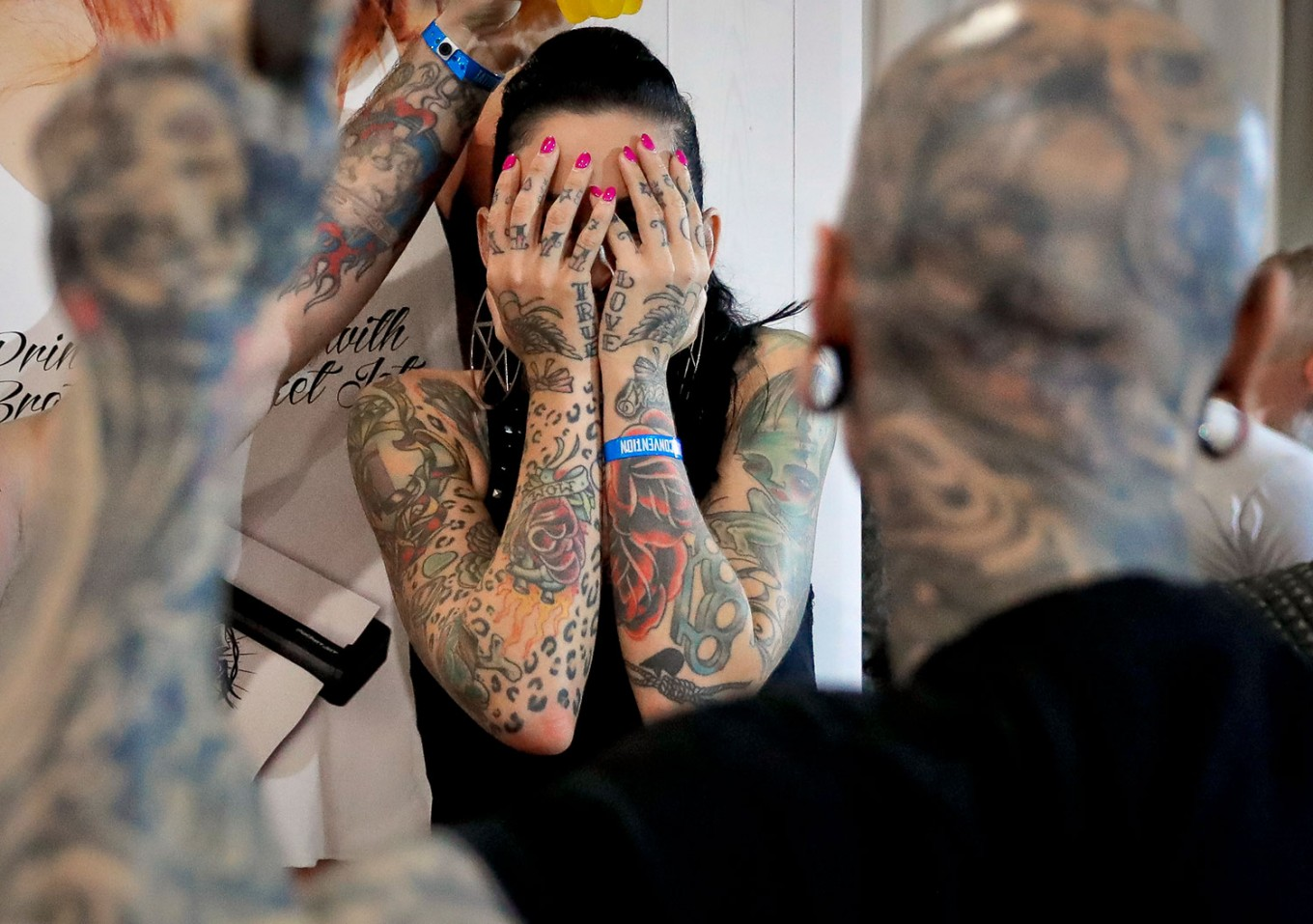 In this picture taken on Sunday, Oct. 16, 2016, a a woman covers her face during the International Tattoo Convention Bucharest 2016 in Bucharest, Romania. More than 100 tattoo and piercing artists brought their skills and art to a three-day convention in the Romanian capital. AP Photo/Vadim Ghirda