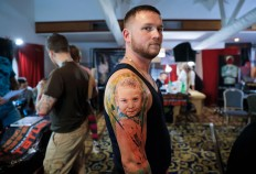In this picture taken on Sunday, Oct. 16, 2016, Serghei, from the Republic of Moldova, poses with a fresh tattoo showing his son Chiril applied to his hand, during the International Tattoo Convention Bucharest 2016 in Bucharest, Romania. AP Photo/Vadim Ghirda