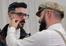 In this picture taken on Sunday, Oct. 16, 2016, a man performs final adjustments on another's mustache during the National Competition for Beards and Mustaches which took place along with the International Tattoo Convention Bucharest 2016 in Bucharest, Romania. More than 100 tattoo and piercing artists brought their skills and art to a three-day convention in the Romanian capital, while men showed off their facial hair in a contest.AP Photo/Vadim Ghirda