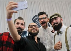 In this picture taken on Sunday, Oct. 16, 2016, men smile while posing for a selfie during the National Competition for Beards and Mustaches which took place along with the International Tattoo Convention Bucharest 2016 in Bucharest, Romania. More than 100 tattoo and piercing artists brought their skills and art to a three-day convention in the Romanian capital, while men showed off their facial hair in a contest.AP Photo/Vadim Ghirda