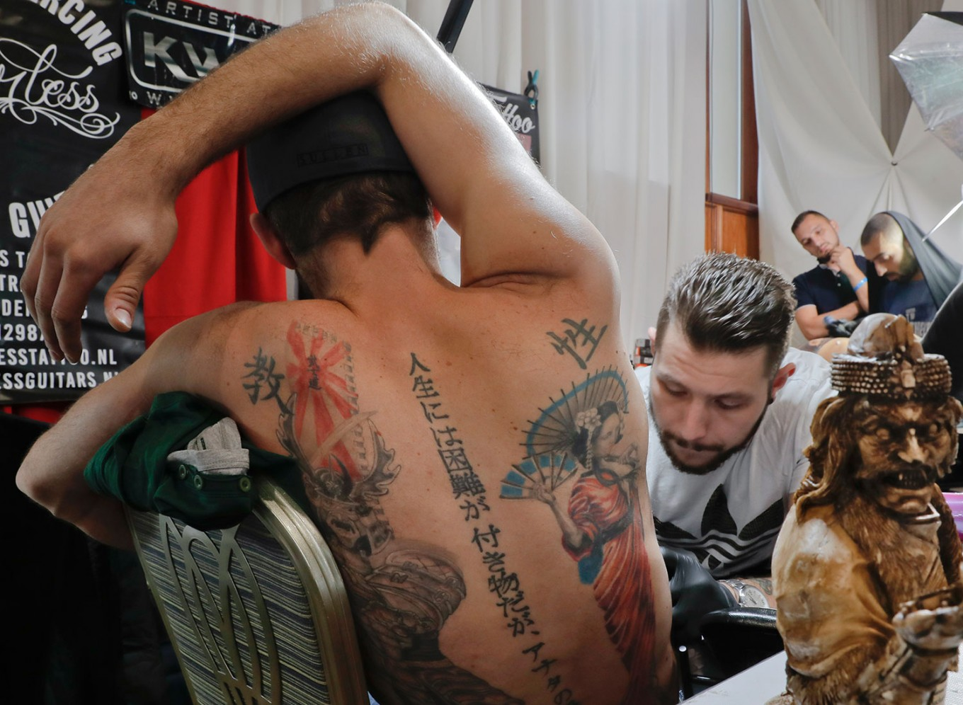 In this picture taken on Sunday, Oct. 16, 2016, a man gets a tattoo during the International Tattoo Convention Bucharest 2016 in Bucharest, Romania. More than 100 tattoo and piercing artists brought their skills and art to a three-day convention in the Romanian capital. AP Photo/Vadim Ghirda