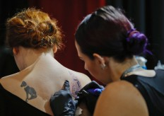 In this picture taken on Sunday, Oct. 16, 2016, a woman gets a tattoo during the International Tattoo Convention Bucharest 2016 in Bucharest, Romania. More than 100 tattoo and piercing artists brought their skills and art to a three-day convention in the Romanian capital. AP Photo/Vadim Ghirda