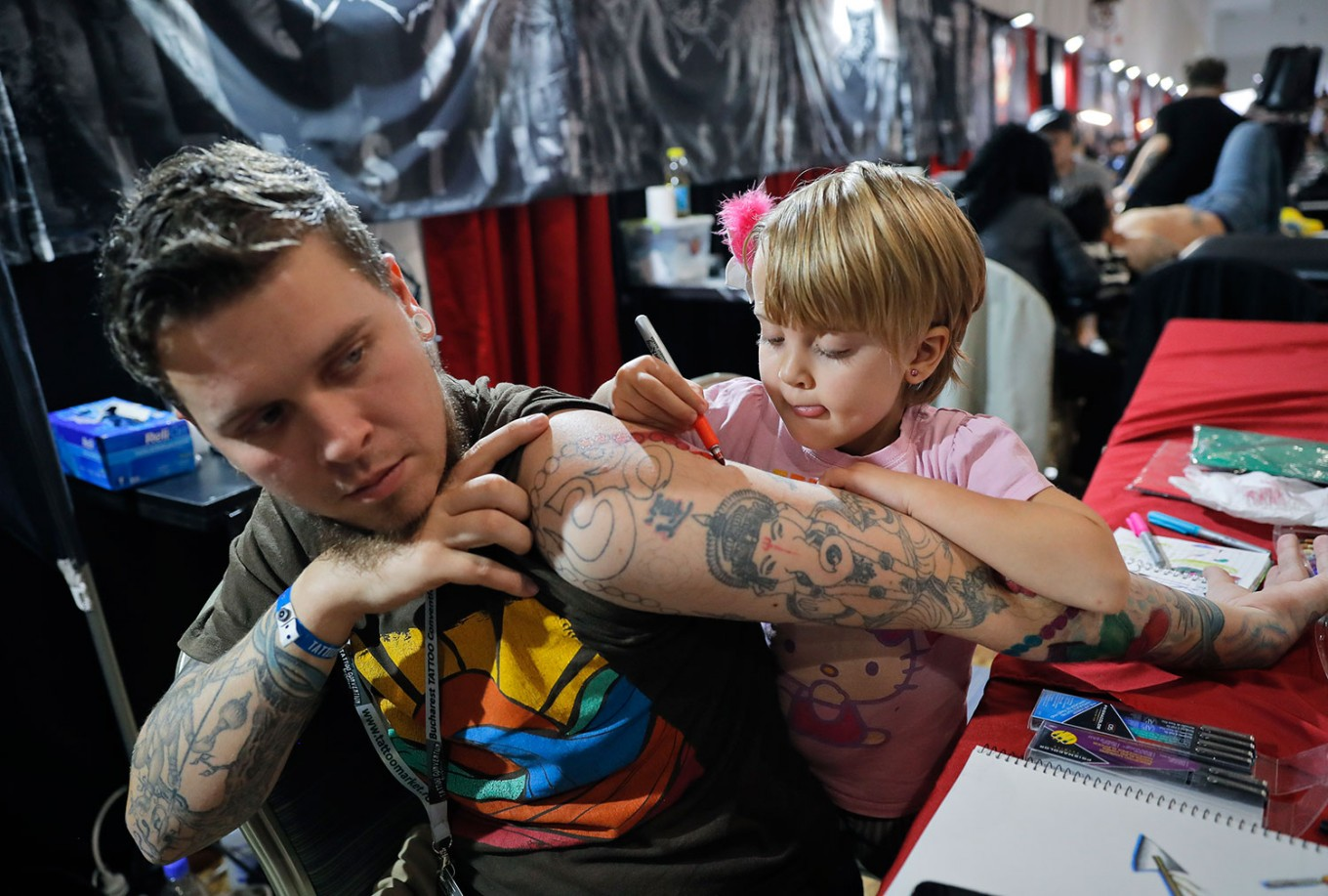 In this picture taken on Sunday, Oct. 16, 2016, Ave, 4 year-old from  the United States, paints on her father's arm during the International Tattoo Convention Bucharest 2016 in Bucharest, Romania. More than 100 tattoo and piercing artists brought their skills and art to a three-day convention in the Romanian capital. AP Photo/Vadim Ghirda