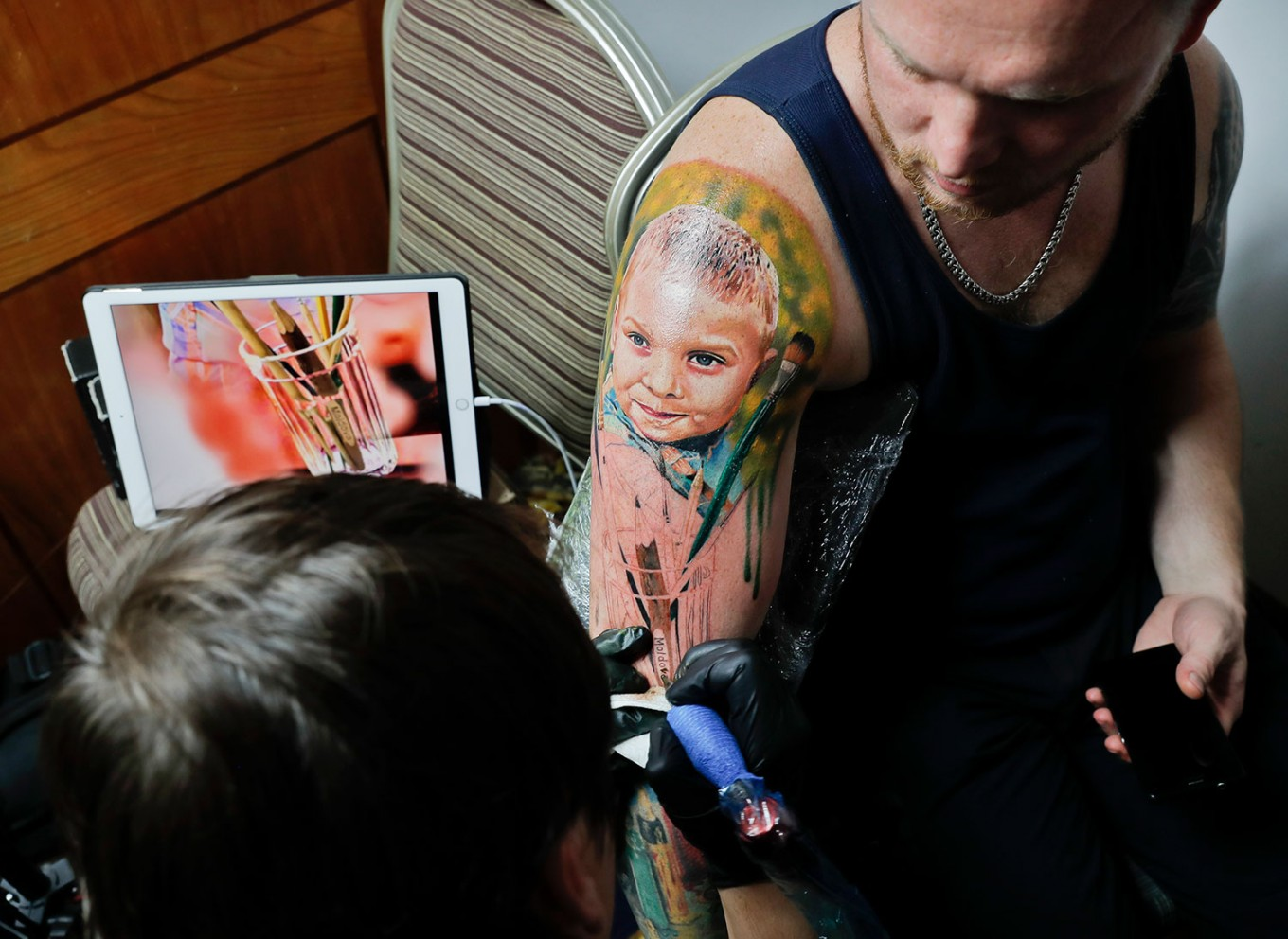 In this picture taken on Sunday, Oct. 16, 2016, Serghei, from the Republic of Moldova, gets a tattoo showing his son Chiril applied to his hand, during the International Tattoo Convention Bucharest 2016 in Bucharest, Romania. AP Photo/Vadim Ghirda