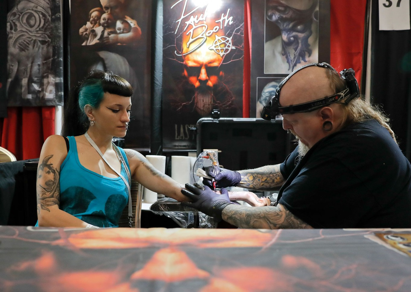 In this picture taken on Sunday, Oct. 16, 2016, Paul Booth of the U.S., one of the world's most famous tattoo artists, works during the International Tattoo Convention Bucharest 2016 in Bucharest, Romania. More than 100 tattoo and piercing artists brought their skills and art to a three-day convention in the Romanian capital. AP Photo/Vadim Ghirda