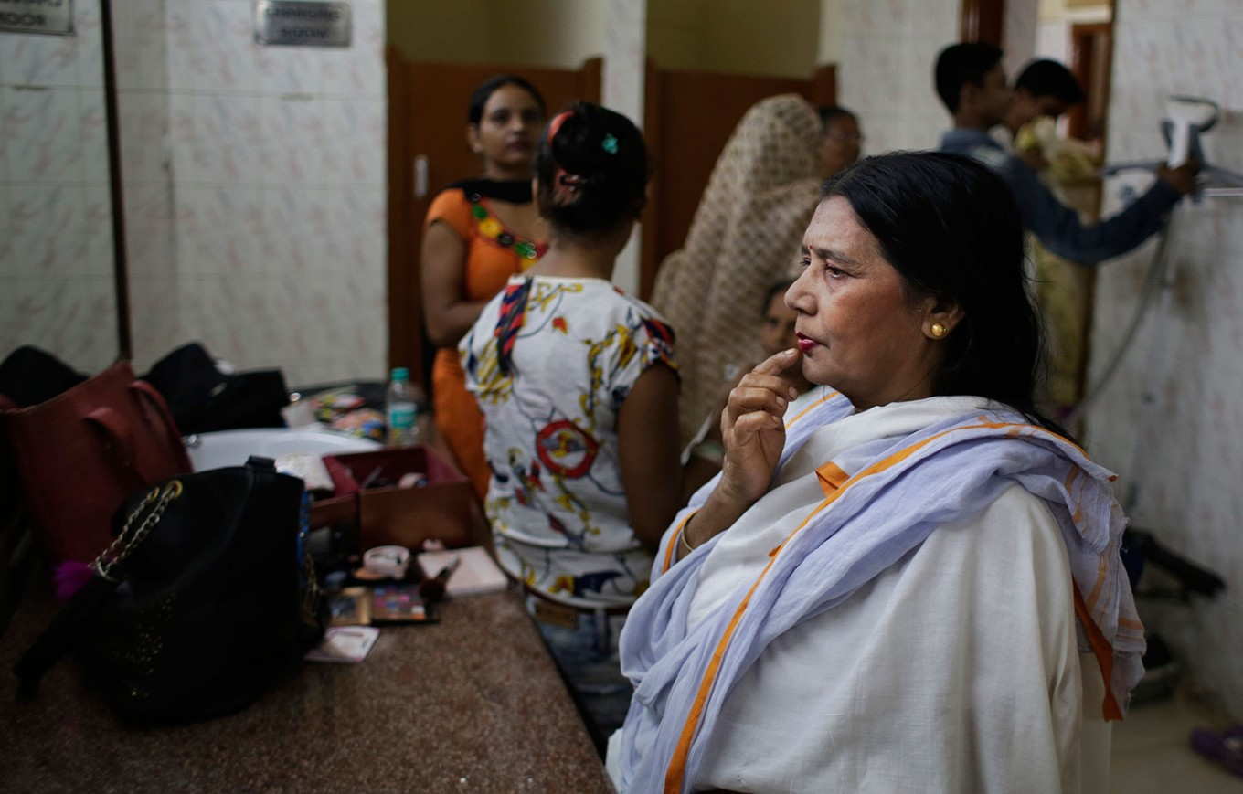 An Indian Hindu widow touches her lips after a make-up artist applied lipstick on it before a fashion show in New Delhi, India, Saturday, Oct. 15, 2016. In most of India, millions of Hindu widows are expected to live out their days in quiet worship, dressed only in white, typically barred from all religious festivities because their very presence is considered inauspicious. But slowly, widows are moving toward modernity. Their lives appear to be changing for better with women's groups and Indian aid organizations taking interest in their welfare. AP Photo/Altaf Qadri