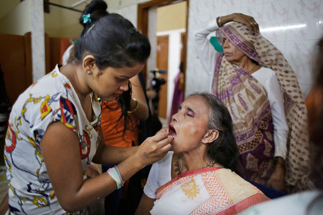 A makeup artist applies lipstick on an Indian Hindu widow before a fashion show in New Delhi, India, Saturday, Oct. 15, 2016. In most of India, millions of Hindu widows are expected to live out their days in quiet worship, dressed only in white. They are typically barred from all religious festivities because their very presence is considered inauspicious. Their lives appear to be changing for better with women's groups and Indian aid organizations taking interest in their welfare. AP Photo/Altaf Qadri