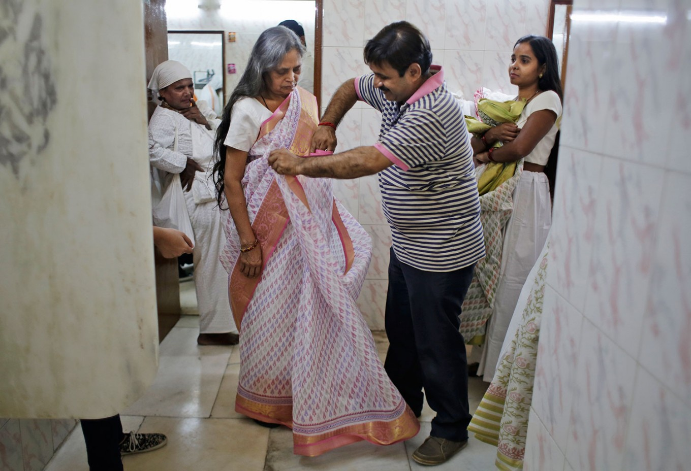 An Indian Hindu widow gets dressed backstage before participating in a fashion show in New Delhi, India, Saturday, Oct. 15, 2016. In most of India, millions of Hindu widows are expected to live out their days in quiet worship, dressed only in white. They are typically barred from all religious festivities because their very presence is considered inauspicious. Their lives appear to be changing for better with women's groups and Indian aid organizations taking interest in their welfare. AP Photo/Altaf Qadri