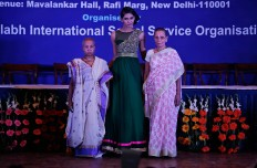 Indian Hindu widows walk with a model, center, during a fashion show in New Delhi, India, Saturday, Oct. 15, 2016. In most of India, millions of Hindu widows are expected to live out their days in quiet worship, dressed only in white. The widows are now breaking age-old traditions of staying aloof by actively participating in Hindu festivals like Holi and Diwali. They went a step further on Saturday, participating in a fashion show. AP Photo/Altaf Qadri