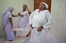 An Indian Hindu widow laughs as she wears a Sari backstage before participating in a fashion show fashion show in New Delhi, India, Saturday, Oct. 15, 2016. Until recently, Indian widows were expected to follow the sociocultural codes of a patriarchal Hindu society that demands a woman lead a life of asceticism after a husband's death. Their lives appear to be changing for better with women's groups and Indian aid organizations taking interest in their welfare. AP Photo/Altaf Qadri