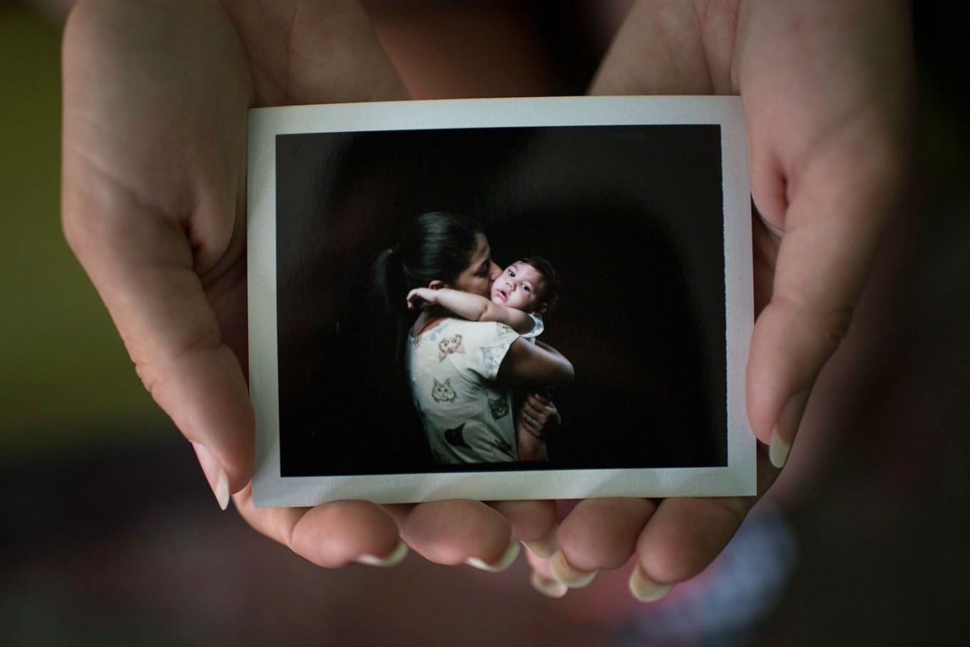 In this Sept. 26, 2016 photo, Angelica Pereira holds a instant film photo of her and her daughter Luiza, who was born with microcephaly, one of many serious medical problems that can be caused by congenital Zika syndrome, in Santa Cruz do Capibaribe, Pernambuco state, Brazil. For a brief moment, mothers with 1-year-old babies with microcephaly, forgot about getting that hard-to-find drug needed to prevent their babies from having seizures or the uncomfortable stares directed at their children born with small heads because of a Zika virus infection in the womb. Instead they were just like any other moms getting the first formal photographs of their babies. AP Photo/Felipe Dana