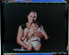 In this Sept. 29, 2016 photo made from a negative recovered from instant film, Vanessa dos Santos poses with her son, Enzo, who was born with microcephaly, one of many serious medical problems that can be caused by congenital Zika syndrome, in Recife, Pernambuco state, Brazil. Santos is one of the few mothers who lives within walking distance of a rehabilitation center. Enzo is eating well and gaining weight, but he has to take medication twice a day to control convulsions and still has difficulties with movements, especially in his hands. AP Photo/Felipe Dana