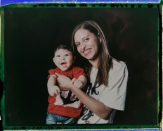In this Sept. 29, 2016 photo made from a negative recovered from instant film, Daniele Ferreira dos Santos holds her son Juan Pedro, who was born with microcephaly, one of many serious medical problems that can be caused by congenital Zika syndrome, as they pose for a photo in Recife, Pernambuco state, Brazil. Santos is helped by her mother and older daughter, who often take turns caring for Juan Pedro. His father left the house a few weeks after he was born. AP Photo/Felipe Dana