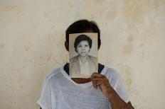 """Ngesti Puji """"Yayuk"""" Rahayu in 2012 holds her own portrait before the Bali bombing. JP/ Anggara Mahendra"""