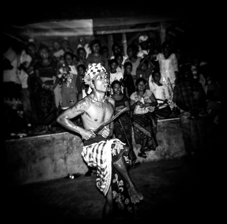 A man in a trance bites a chick while dancing during the battle of effigy deities, Dewa Masraman, at Panti Timbrah Temple in Paksebali village. JP/ Agung Parameswara