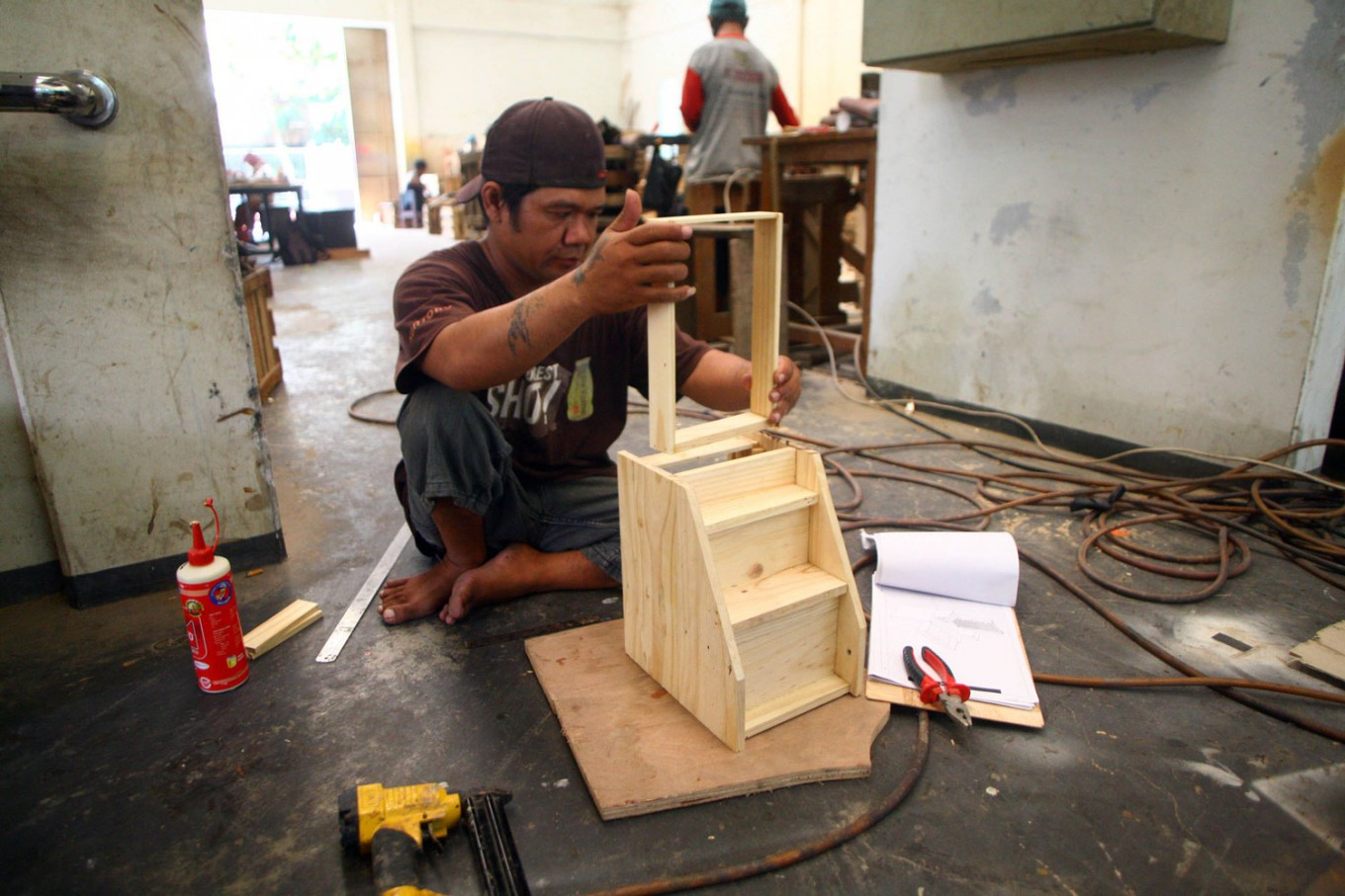 A craftsman makes a miniature vanity table at the Mandiri Craft workshop. JP/Aditya Sagita