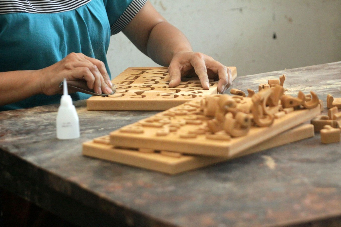 A craftsperson sands a toy puzzle made from mahogany. JP/Aditya Sagita