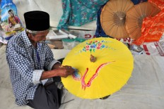 An umbrella maker from Kaliwungu, Kendal, Central Java, decorates an umbrella using oil paints. Customers are primarily attracted to umbrellas painted with flowers and animals. JP / Kus Hendratmo