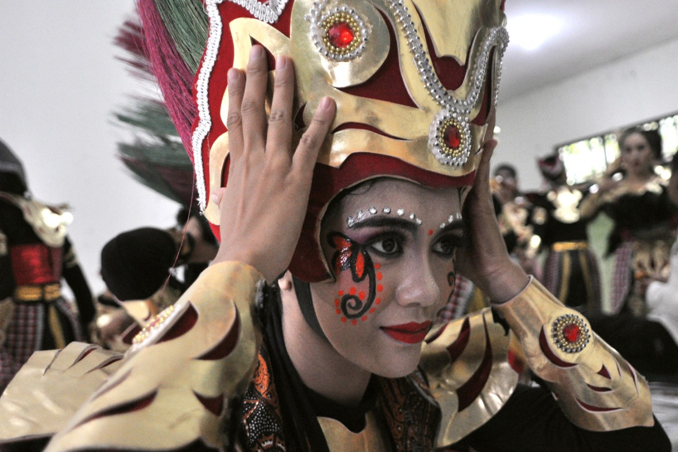 A Topeng Ireng dancer from Boyolali, Central Java, puts on her headdress before a