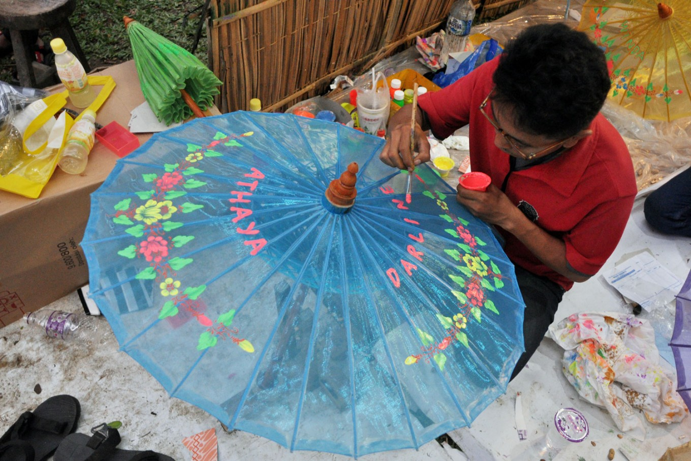 A man paints a name on an umbrella during the 2016 Indonesian Umbrella Festival. Umbrellas decorated with names, produced by artisans from Juwiring, Klaten,