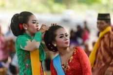 A tayub dancer helps a fellow dancer do her hair. JP/ Tarko Sudiarno