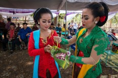 Two tayub dancers sprinkle rose and jasmine petals to mark the beginning of the ritual. JP/ Tarko Sudiarno