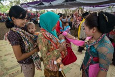 Two women bring their babies forward to ask  for blessings from tayub dancers. JP/ Tarko Sudiarno