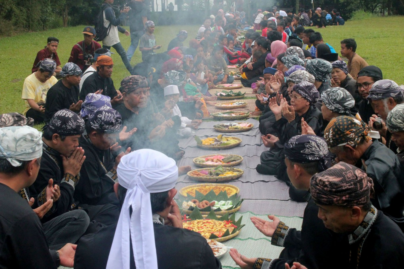 Sindangbarang community leaders and residents pray together before they eat various foods served in the Sedekah Kue [cake offering] ceremony. Everyone brings food from their homes and they eat it together in the ceremony. JP/ Theresia Sufa