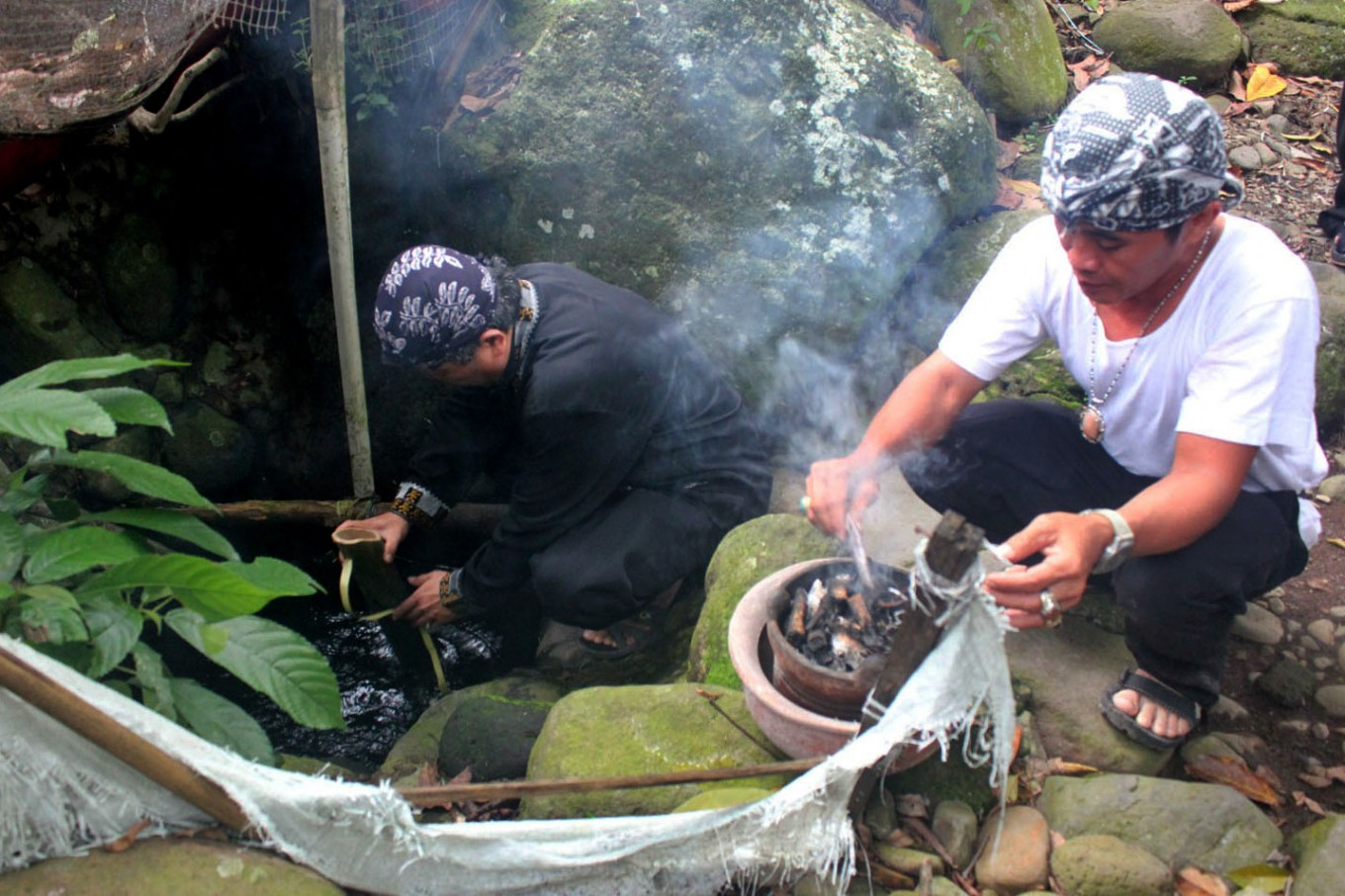Two community leaders, locally known as kokolot, take water from a spring in the Sindangbarang traditional kampung, Tamansari district, Bogor, during the Seren Taun Guru Bumi ceremony. JP/Theresia Sufa