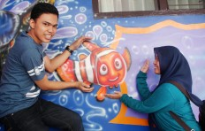Brawijaya university students Aldi and Dwi Setyawati enjoy a moment with the famous cartoon fish. JP/ Suherdjoko