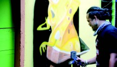 Self-taught artist Eddy Gimbal decorates the children zone. JP/ Suherdjoko