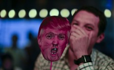 A man laughs as he holds a defaced Donald Trump mask during the election night party at a bar in Buenos Aires, Argentina, Tuesday, Nov. 8, 2016.The United States headed for the polls to vote for their new president. AP Photo/Natacha Pisarenko