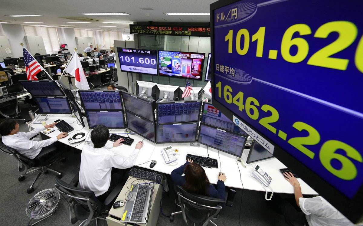 Money traders watch computer screens with the day's exchange rate between yen and the U.S. dollar at a foreign exchange brokerage in Tokyo, Wednesday, Nov. 9, 2016.  Asian shares have shed early gains, tumbling Wednesday as Donald Trump gained the lead in the electoral vote count in the presidential election. Dow and S&P futures also plunged. Earlier, investors had appeared persuaded that Hillary Clinton, seen as a more stable choice, would prevail. AP Photo/Shizuo Kambayashi