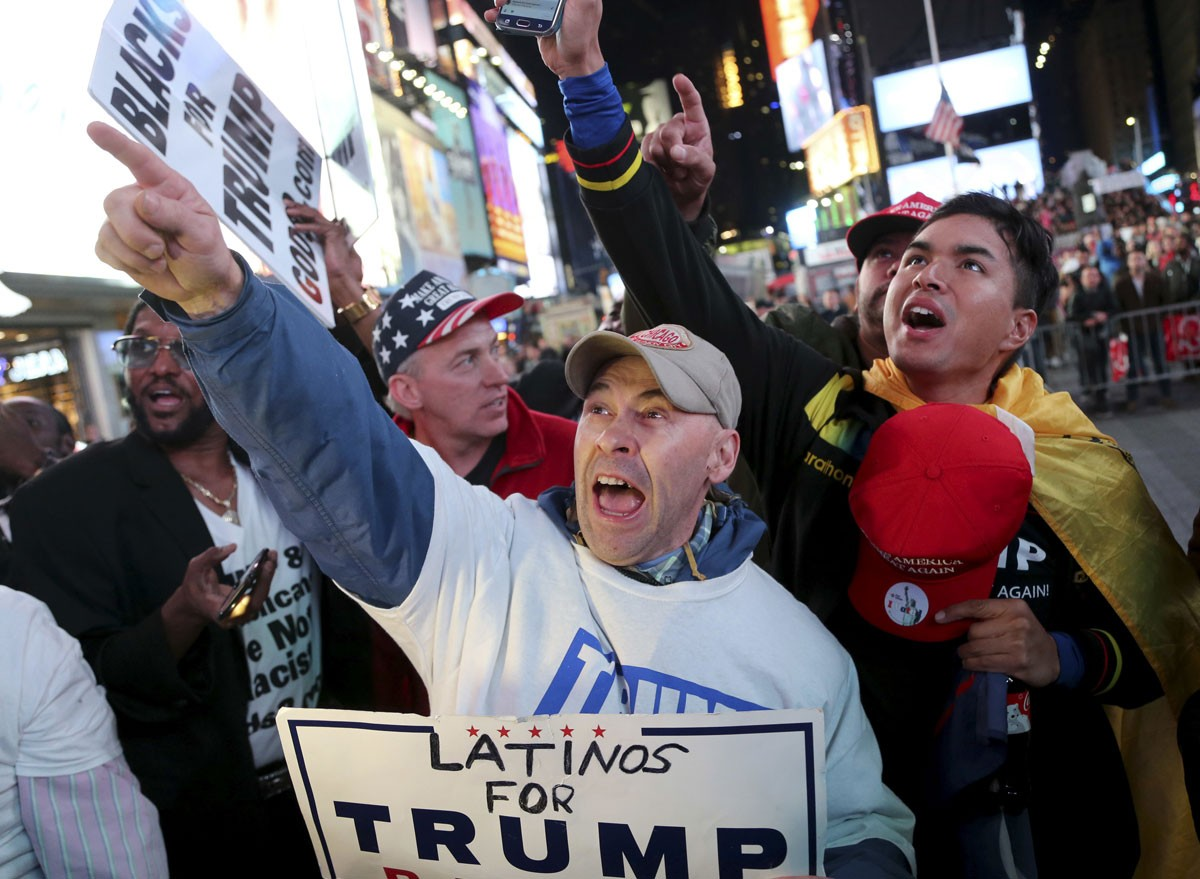 Supporters of Republican presidential candidate Donald Trump react to reports that he had won North Carolina while they were watching results in Times Square, New York, Tuesday, Nov. 8, 2016. AP Photo/Seth Wenig