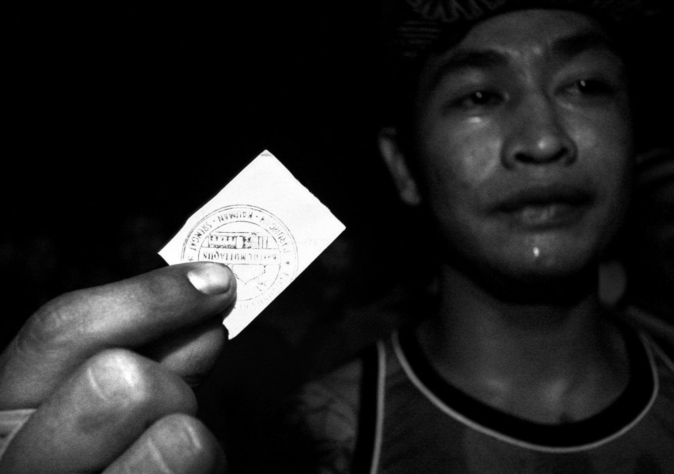 A fighter holds up his coupon entitling him to a plate of chicken soup and rice. JP/ Aman Rochman