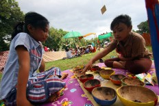 Two girls play mancala using coconut shells during the ninth Children's Gamelan Parade in Yogyakarta.  JP/ Aditya Sagita