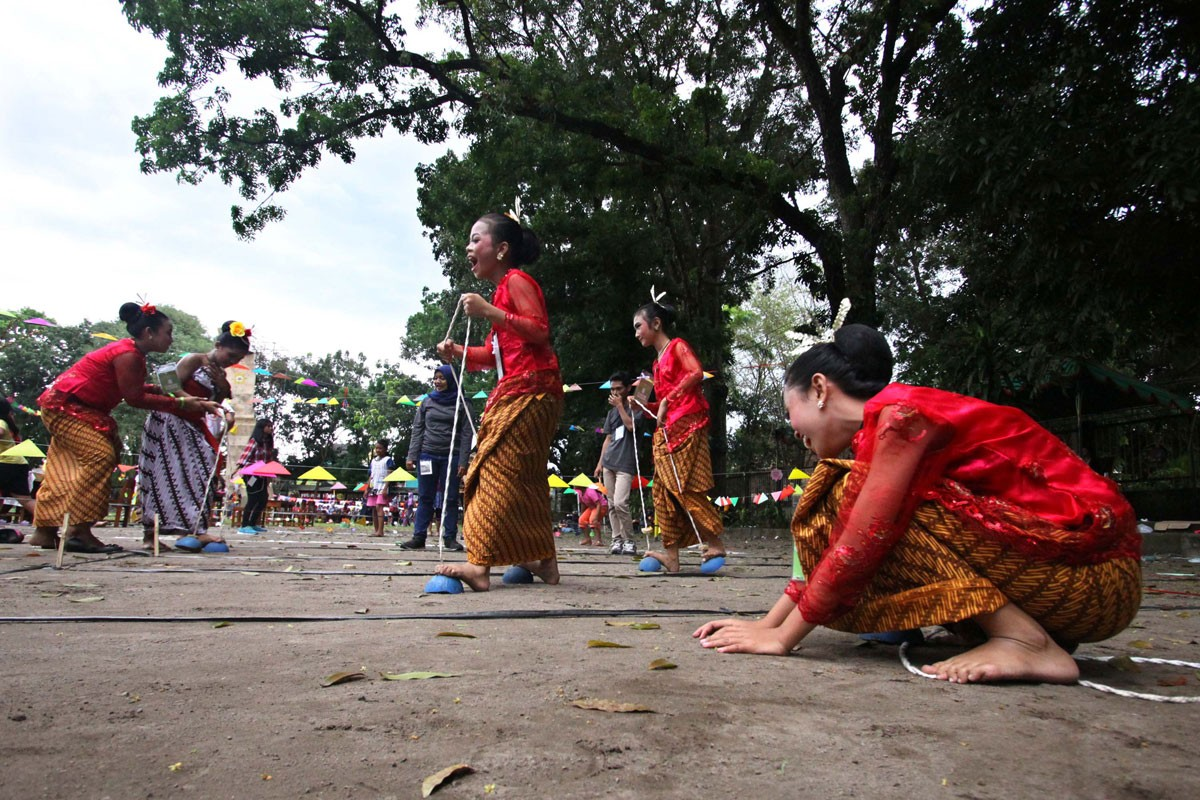 Children race while wearing half coconut shells on their feet, connected to string, in the egrang batok game during the event in Yogyakarta.  JP/ Aditya Sagita