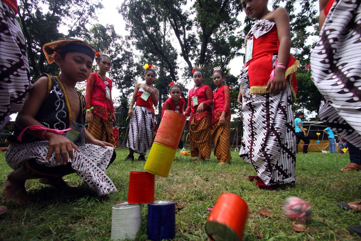 Children wearing traditional costumes play boi-boian, a game requiring two groups of at least five children. The game involves using a ball of crumpled paper to hit a pyramid of cans.  JP/ Aditya Sagita