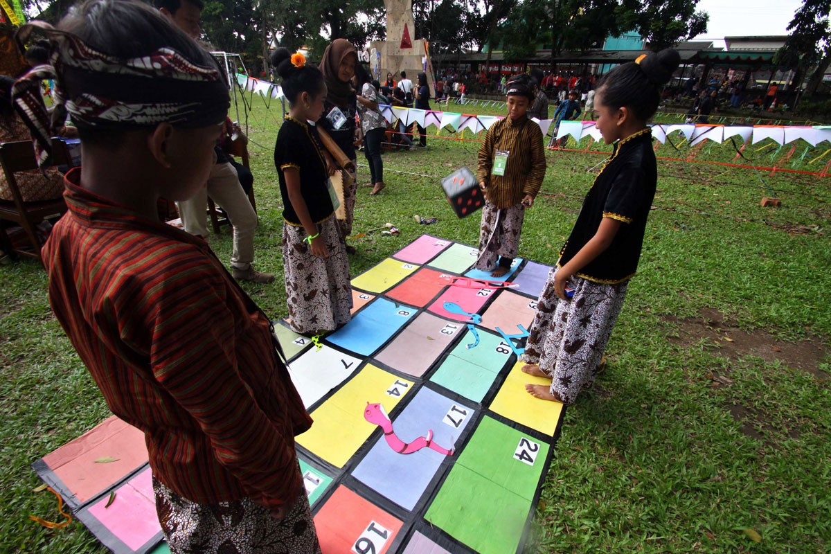 Four children play a giant version of the snakes and ladders board game during the parade organized by Sanata Dharma University. JP/ Aditya Sagita
