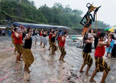 Dressed as the wayang character Petruk, a troupe of young dancers refuses to let the rainy day affect its performance. JP/ Tarko Sudiarno