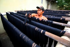 A man checks yarn that is being dried in the sun after dyeing. JP/Aditya Sagita