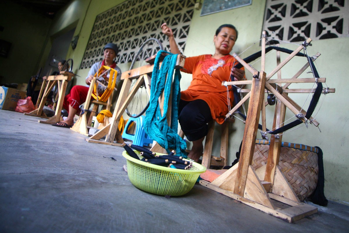 Women spin the yarn before putting it through the warping process. JP/Aditya Sagita