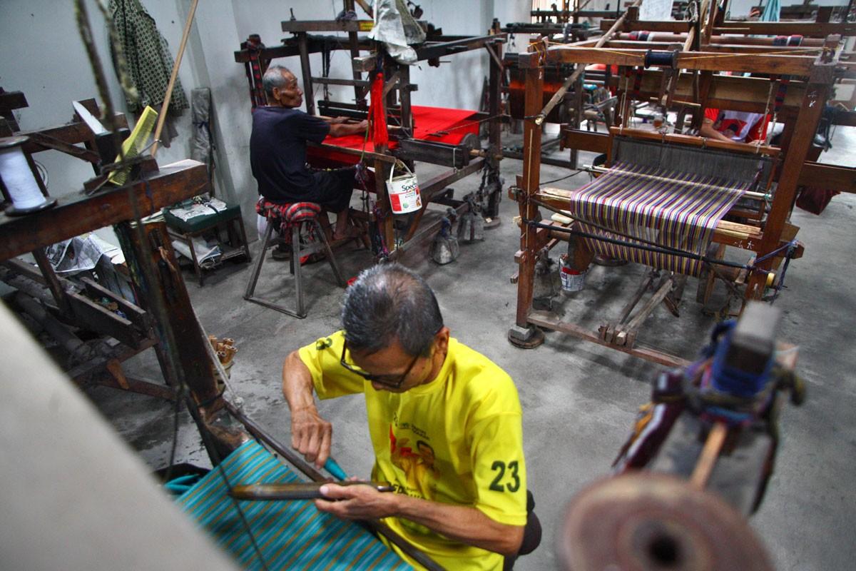 Two men work on lurik cloths using a manual weaving machine. JP/Aditya Sagita