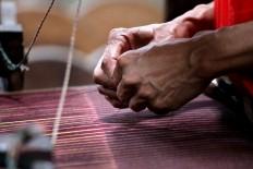A worker prepares the yarn for weaving. JP/Aditya Sagita