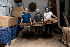 Three workers pose for a picture in the Rizona Baru cigar factory in Temanggung, Central Java. Temanggung is known as a tobacco producing regency in Indonesia. JP/Agung Parameswara