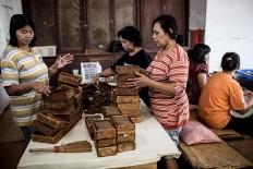 Workers put cigars into boxes at the Rizona Baru factory in Temanggung, Central Java. JP/Agung Parameswara