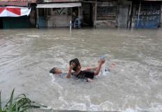 Two children frolic in a flooded road in Jagalan, Jebres in Surakarta, Central Java. JP/ Ganug Nugroho Adi