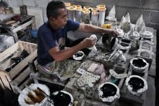 A man pours resin into a mold to make miniature Prambanan temples.JP/Magnus Kushendratmo